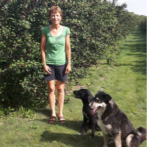 Dr. Diana Durling and her two dogs in front of a row of hedges