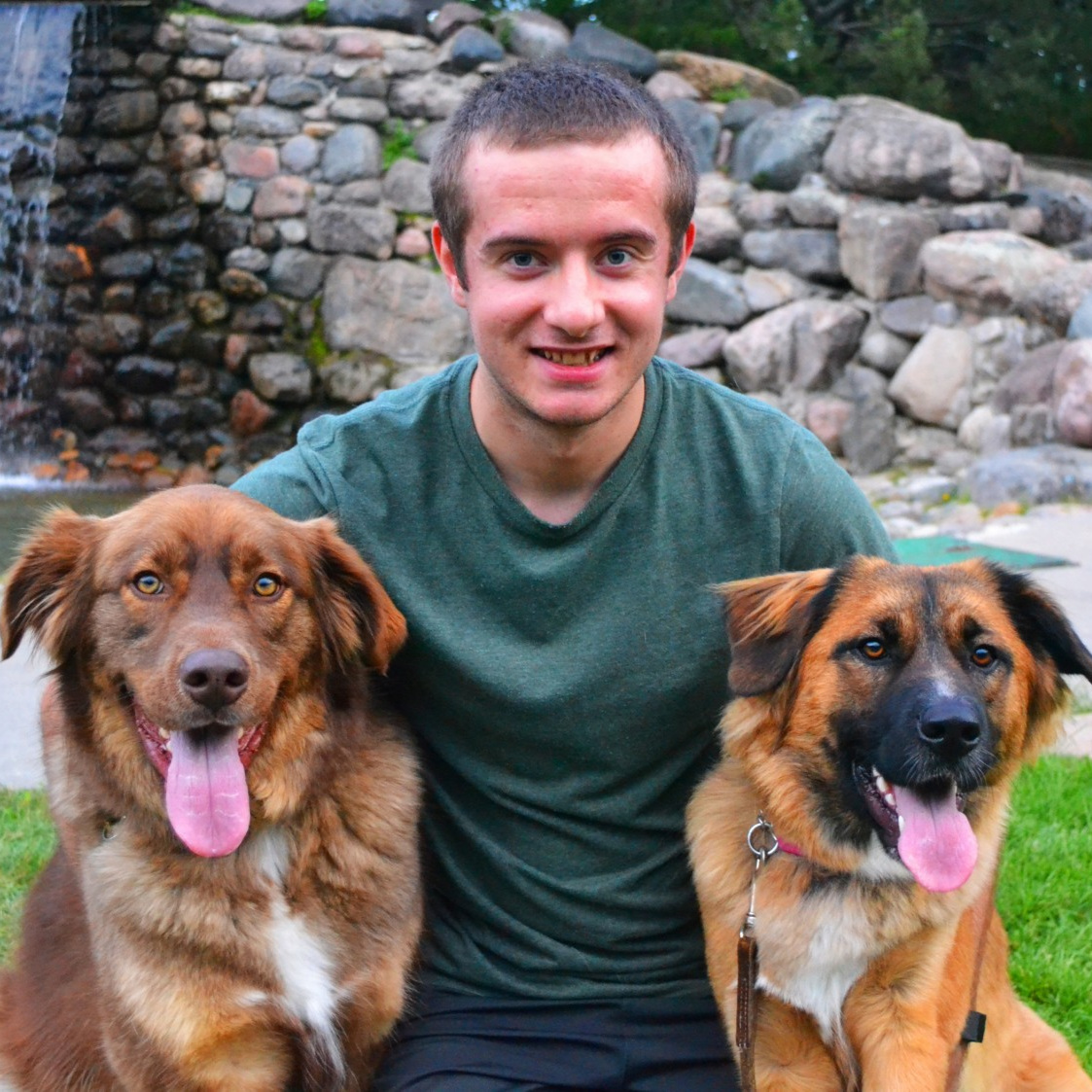 Scott Pilon with two dogs in front of a stone wall