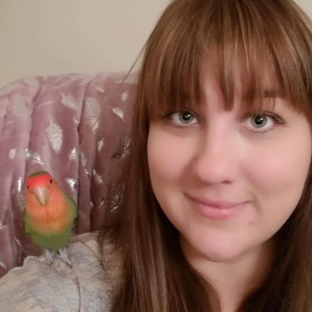 Charlene Trithart with a lovebird on her shoulder