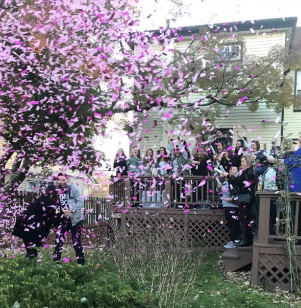 Cannons filled with pink confetti reveal the gender of this couple's baby at their gender reveal party. | LYFETYMES party planning blog has the BEST ideas to reveal your baby's gender at a party with friends and family!