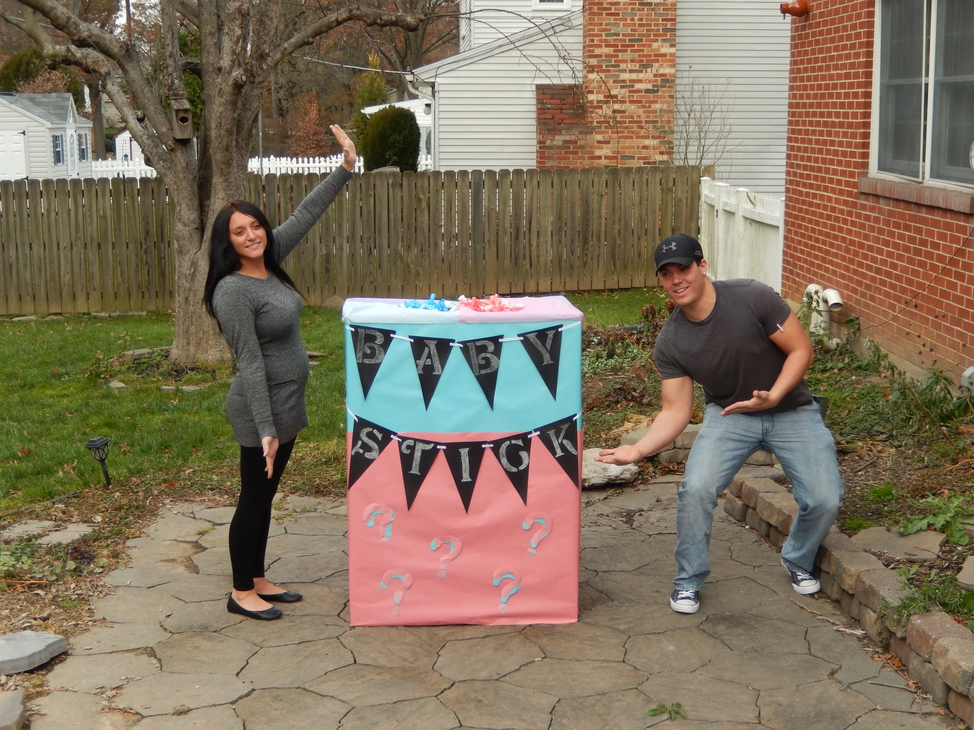 A couple poses right before they reveal their baby's gender using a giant box filled with blue or pink helium balloons. | LYFETYMES party planning blog as an epic list of gender reveal party ideas today on the blog!