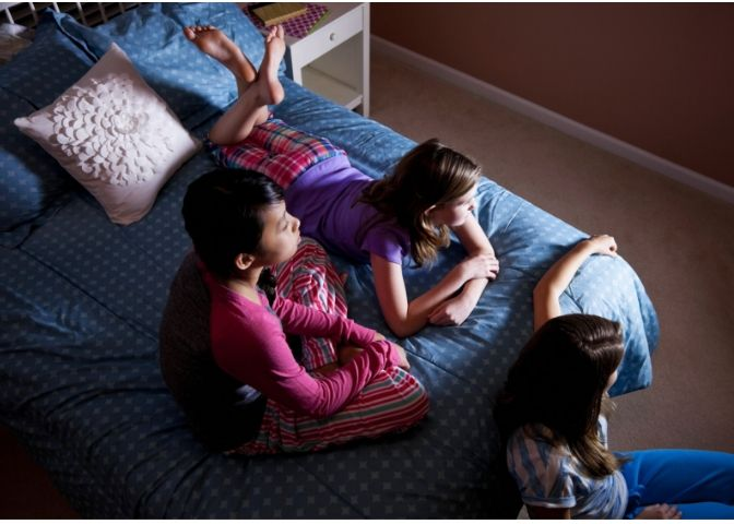 girls watching a movie on a bed