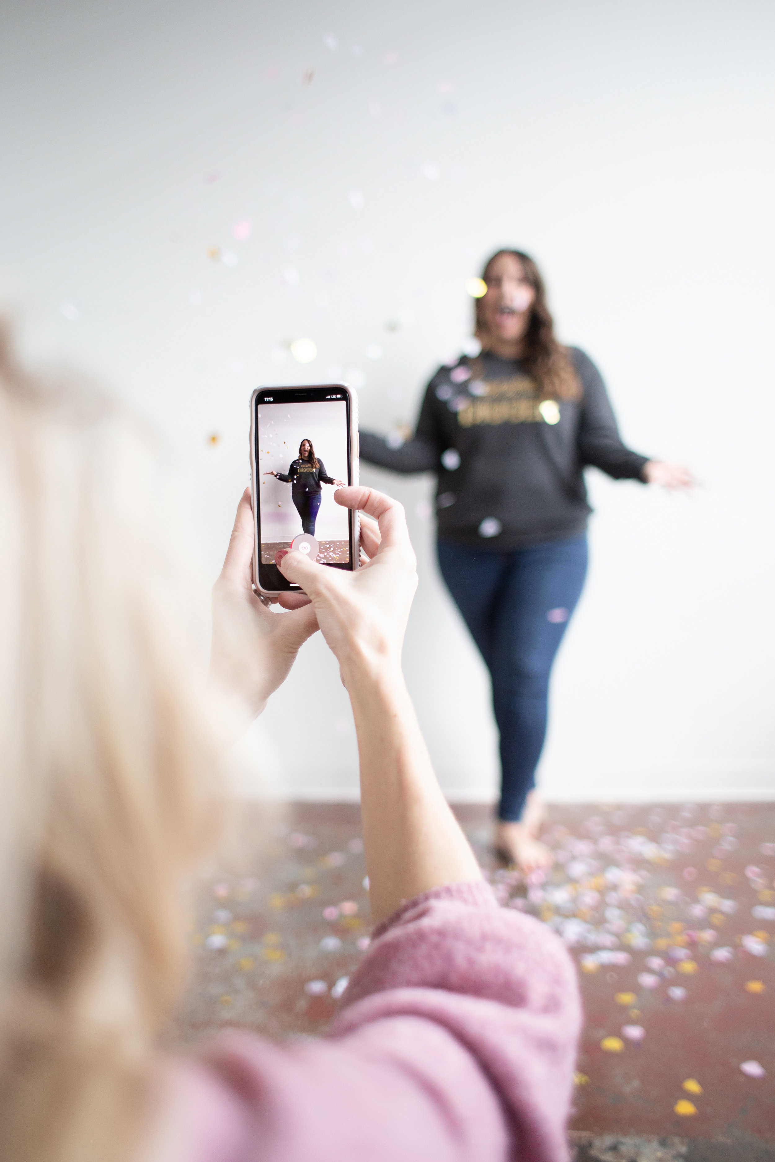 person taking a photo of a woman with glitter on her smart phone