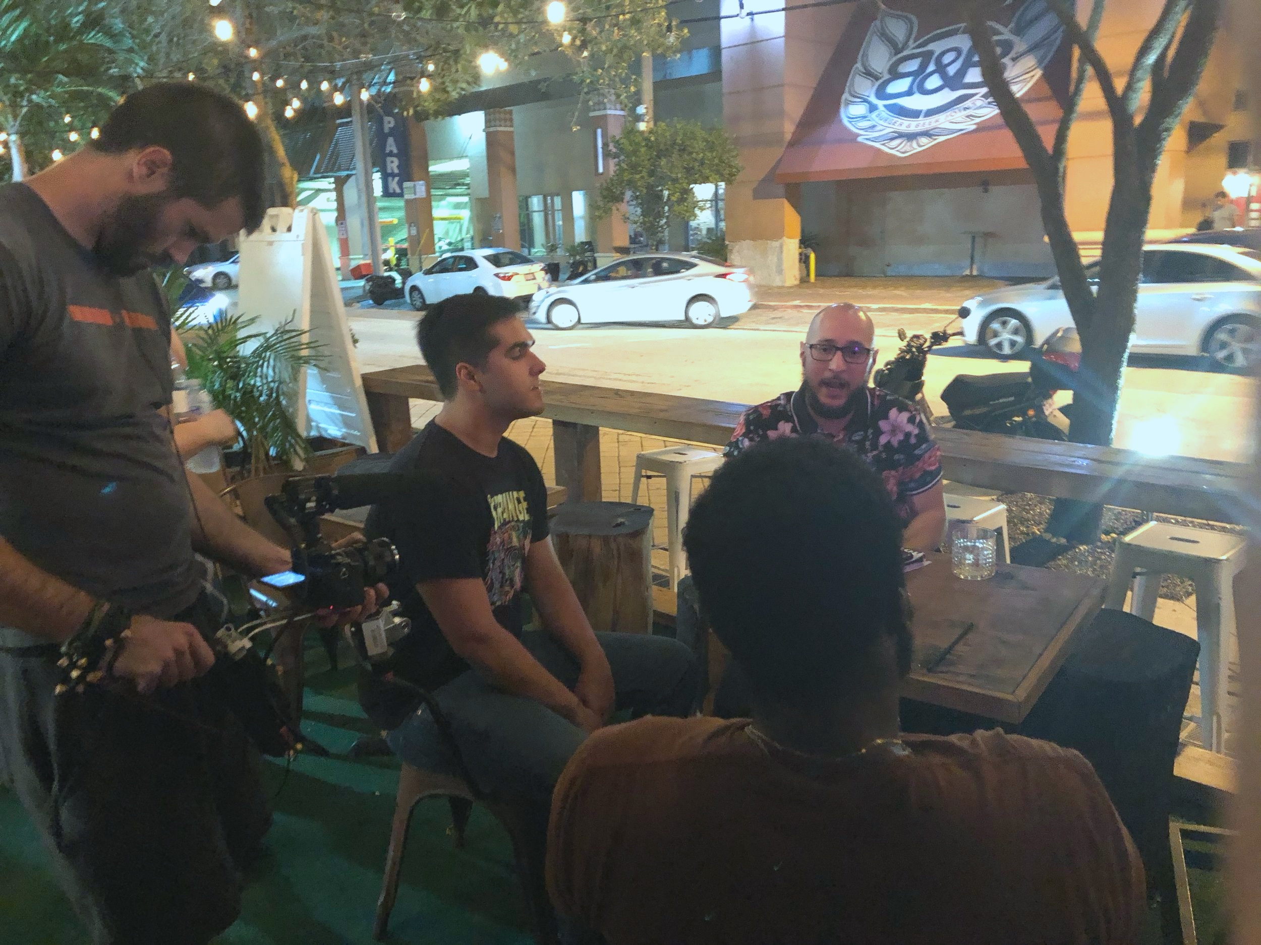 Cinematographer Greg Kerrick films Sebastian Mattar & Rudy Wilson while they chat with friends and comics outside of a Miami Comedy show at Redbar in Brickell, Miami.