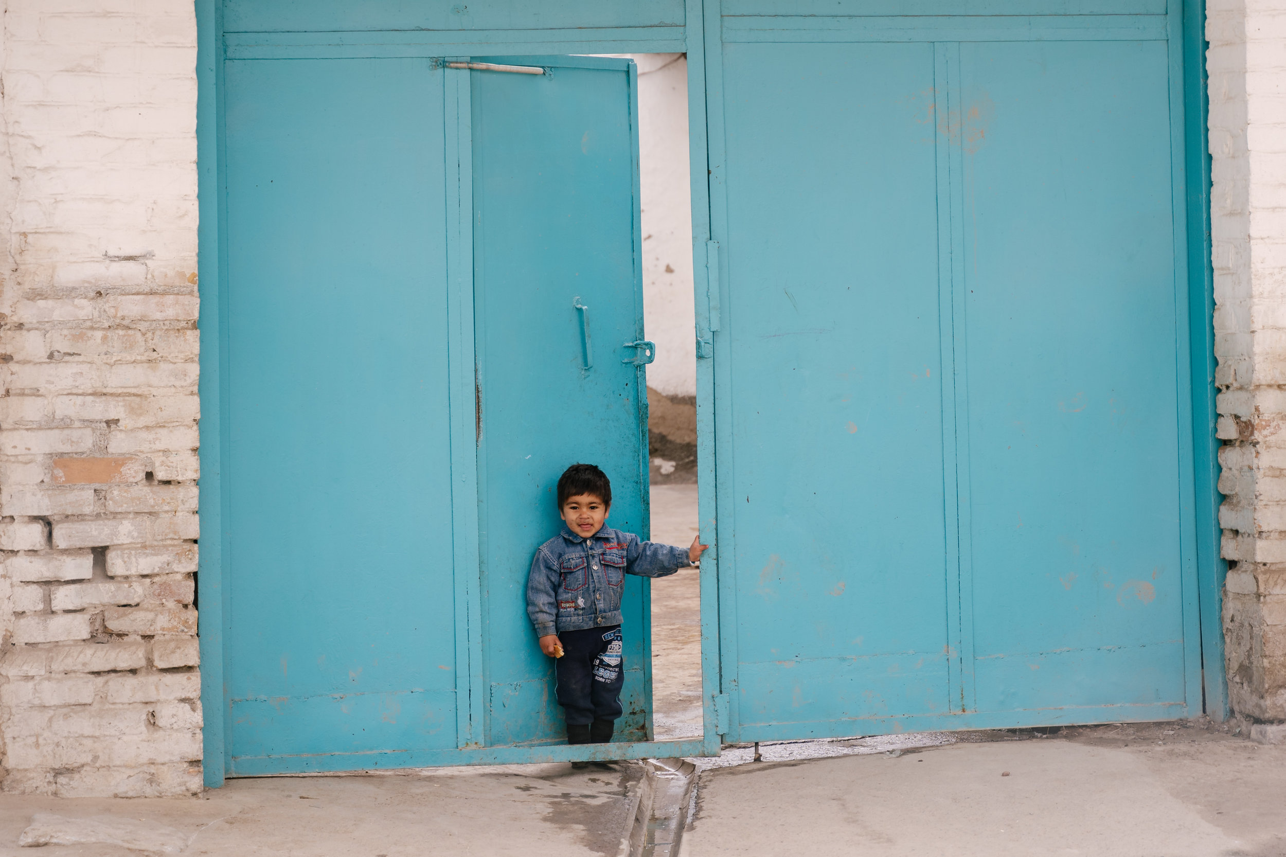A child at the front gate of his house.