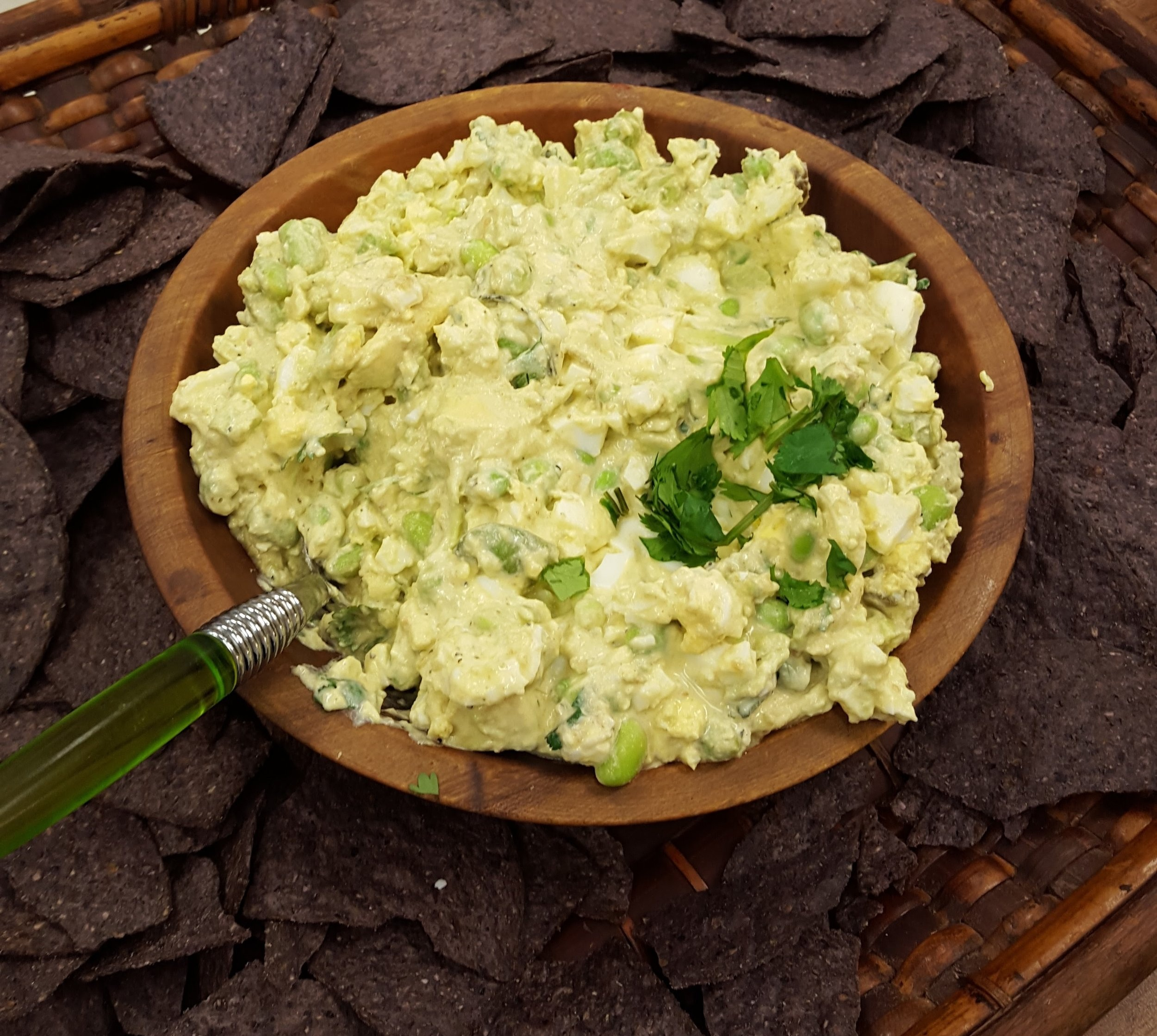 Egg Salad Guacamole with Edamame served with blue corn chips.