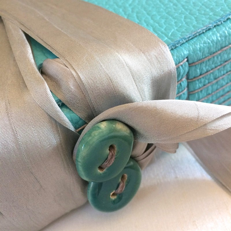Button and ribbon tie on leather baby memory book