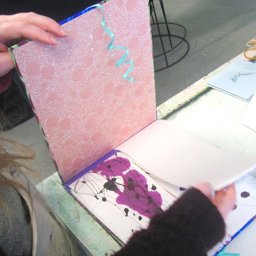 Colourful artist's book with pink paint