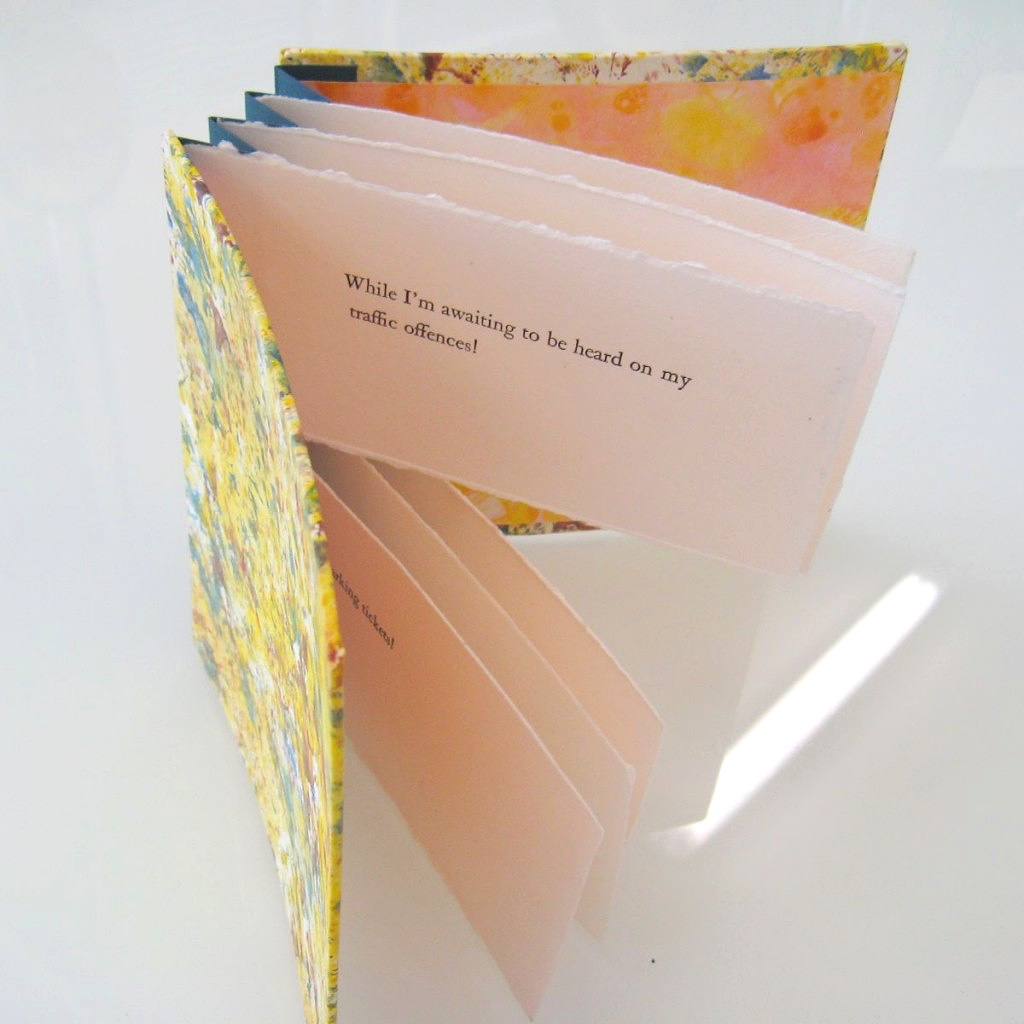 Handmade book with yellow cover and flag pages