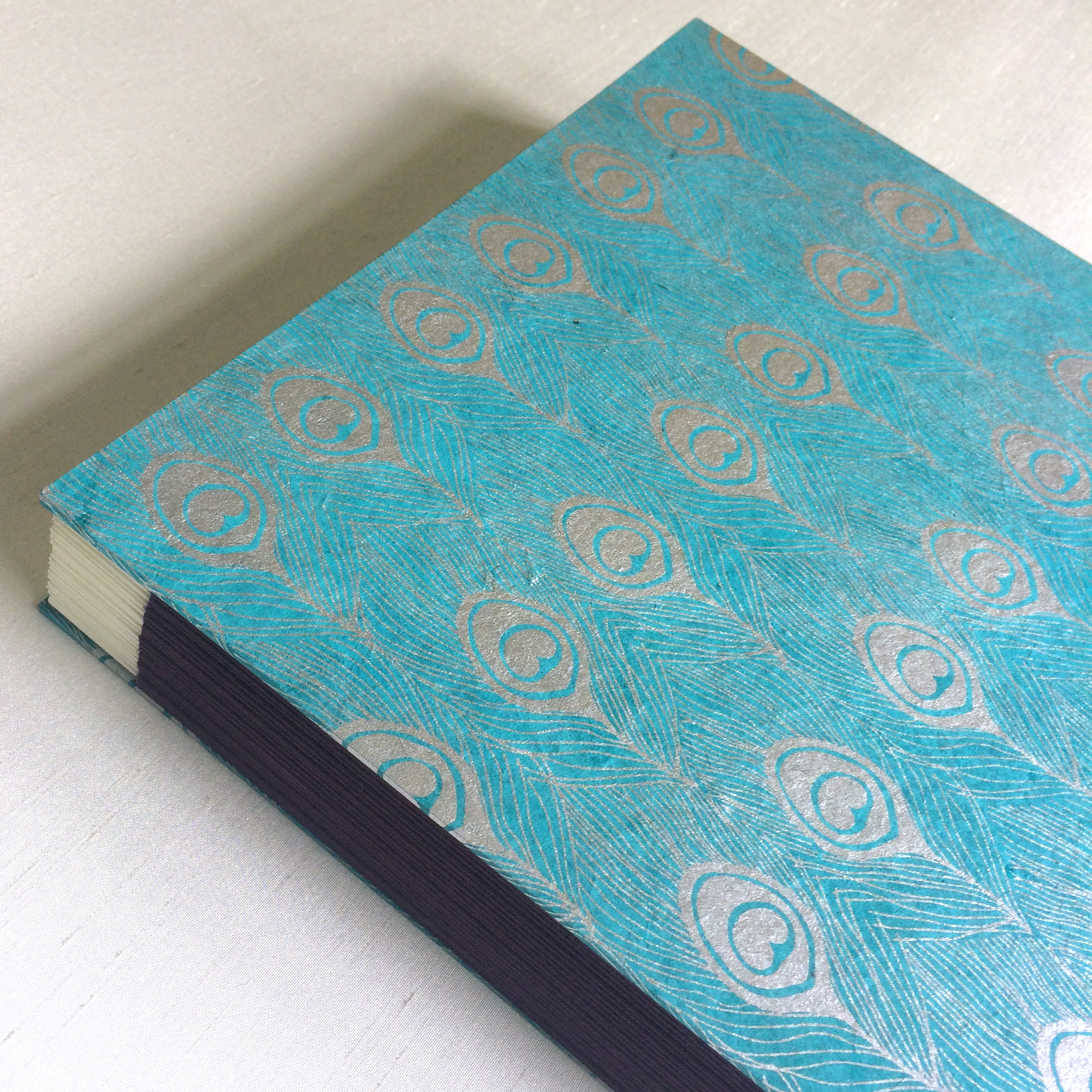 Handmade paper with peacock feather on cover of handcrafted photograph album