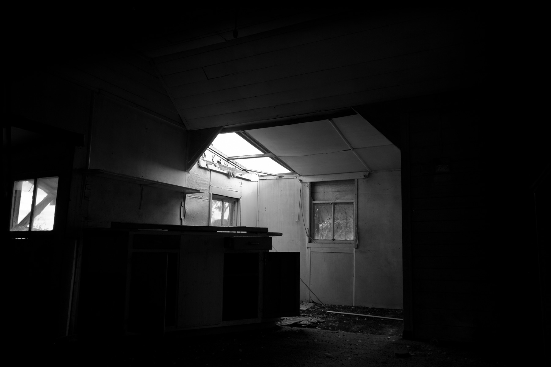 Light coming through a hole in the roof of an abandoned house in Acland