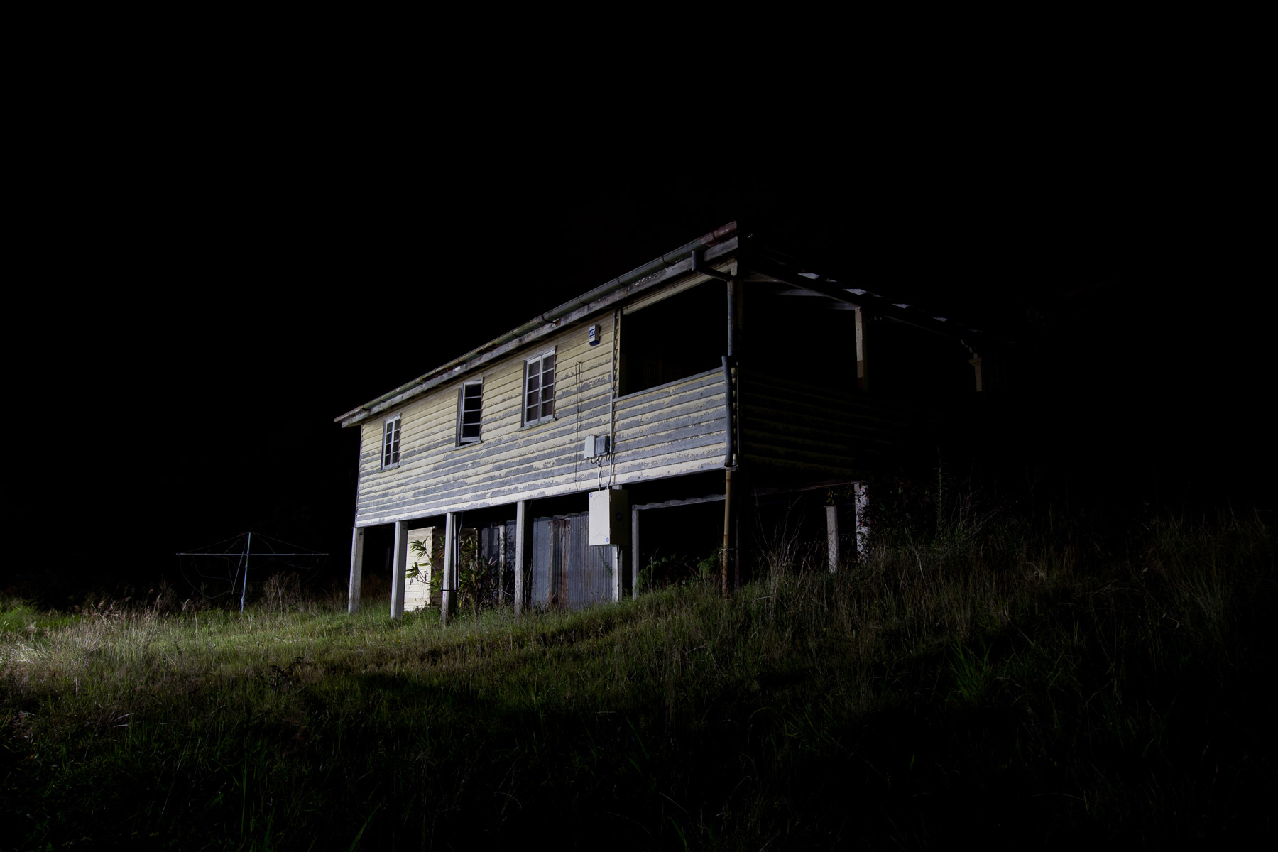 Light hitting the side of an abandoned house at night