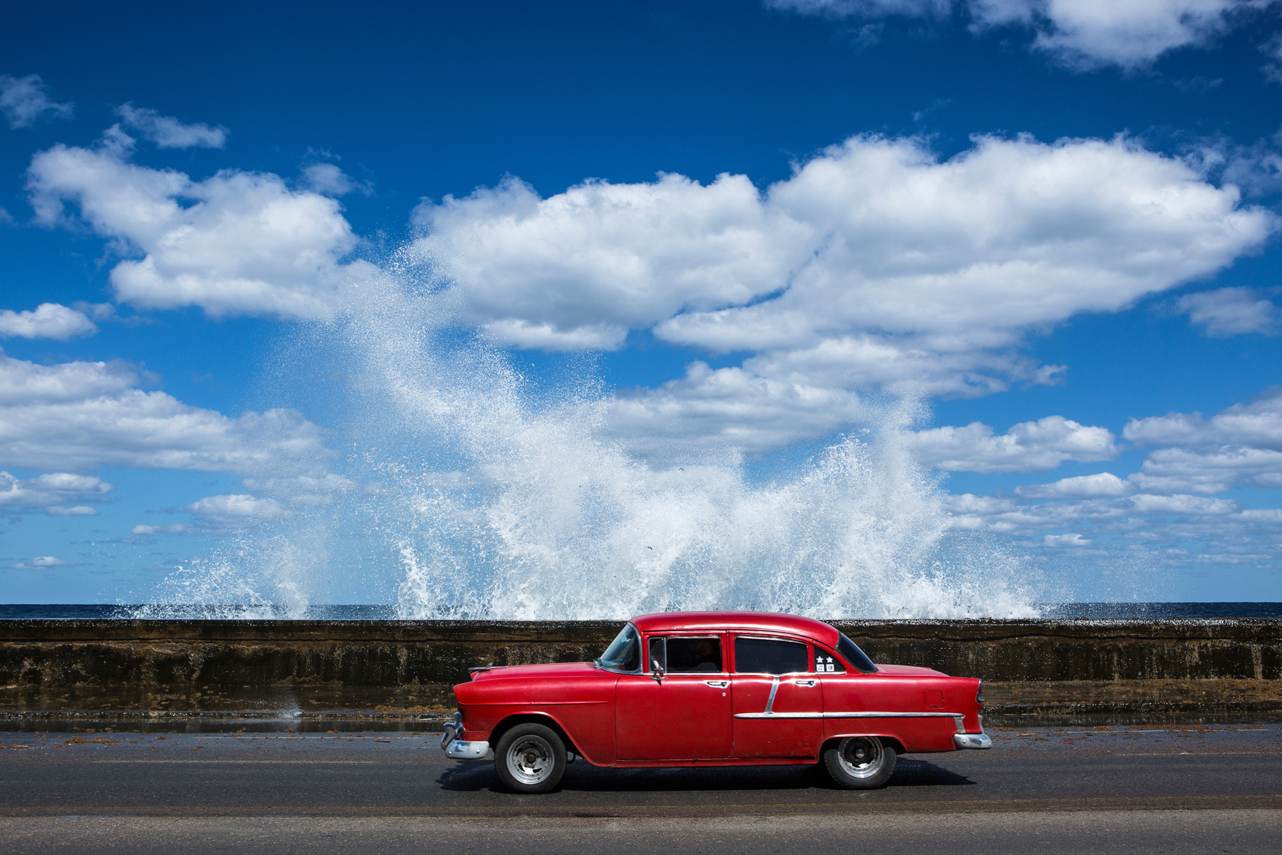 Waves splashing behind a classic American car on the Malecon in Havana, Cuba