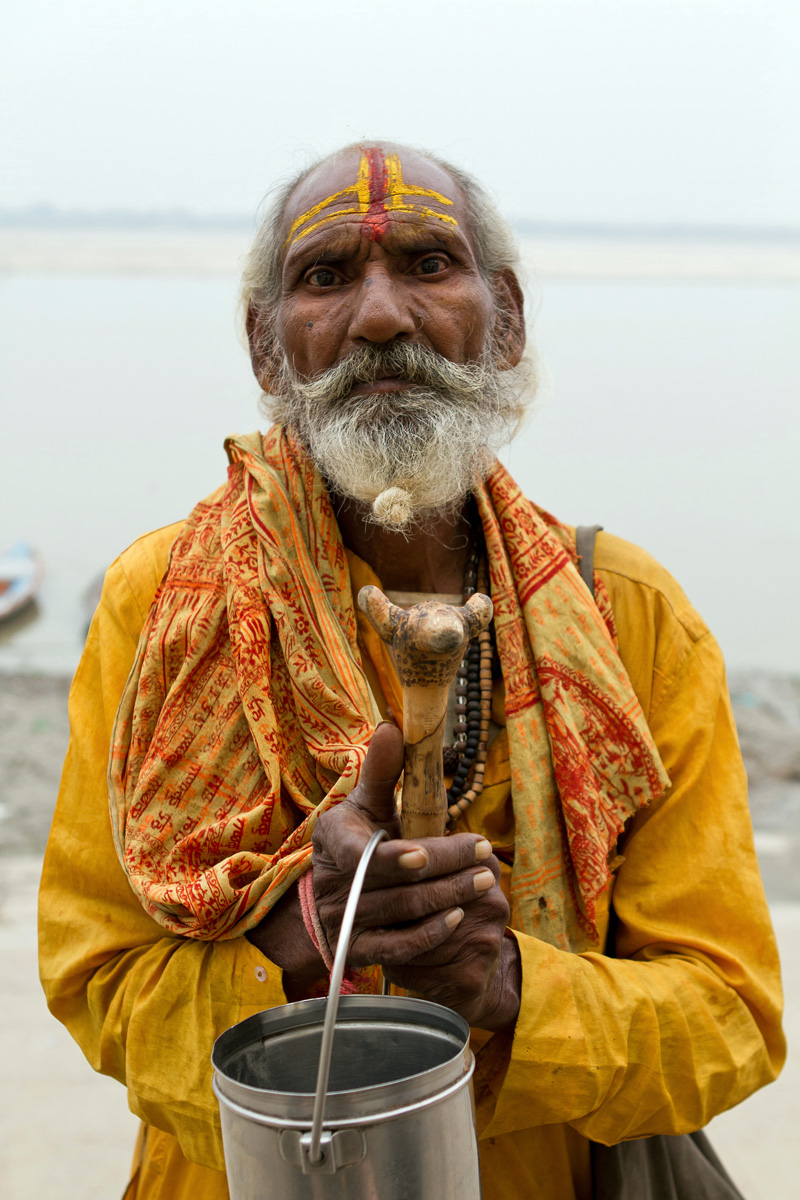 A holy man standing in front of the Ganges River in Varanasi, India