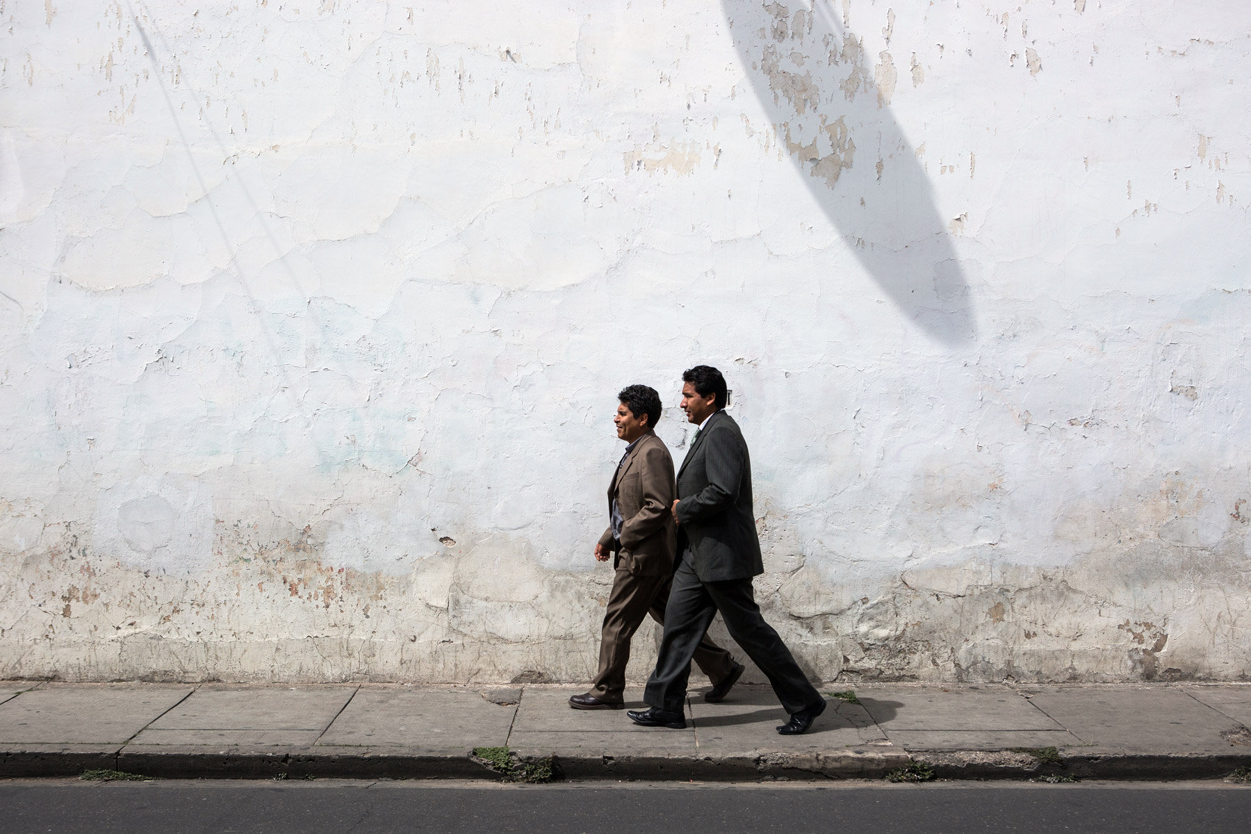 2 men walking in front of a white wall in Sucre, Bolivia