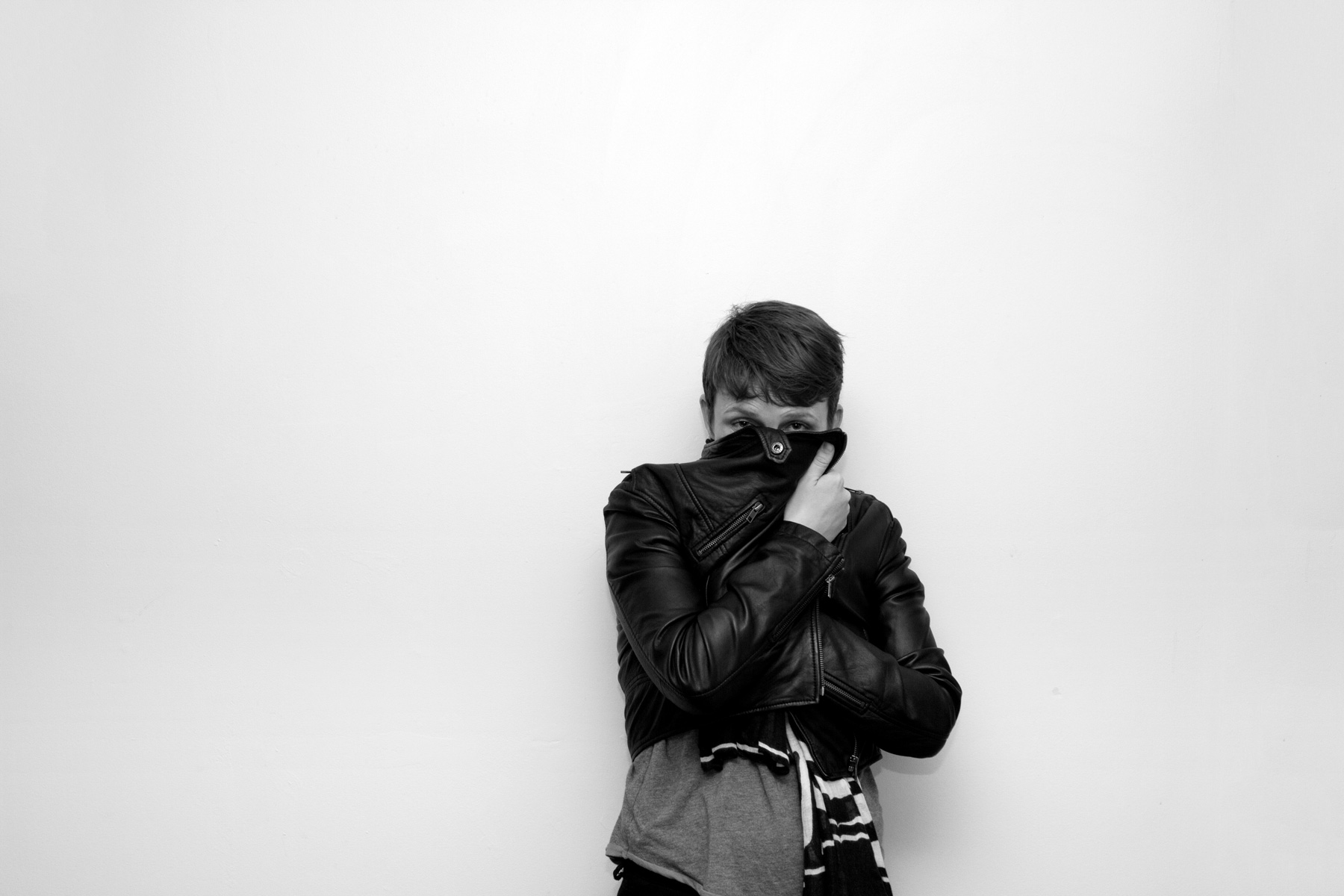 A woman holding her jacket across her face