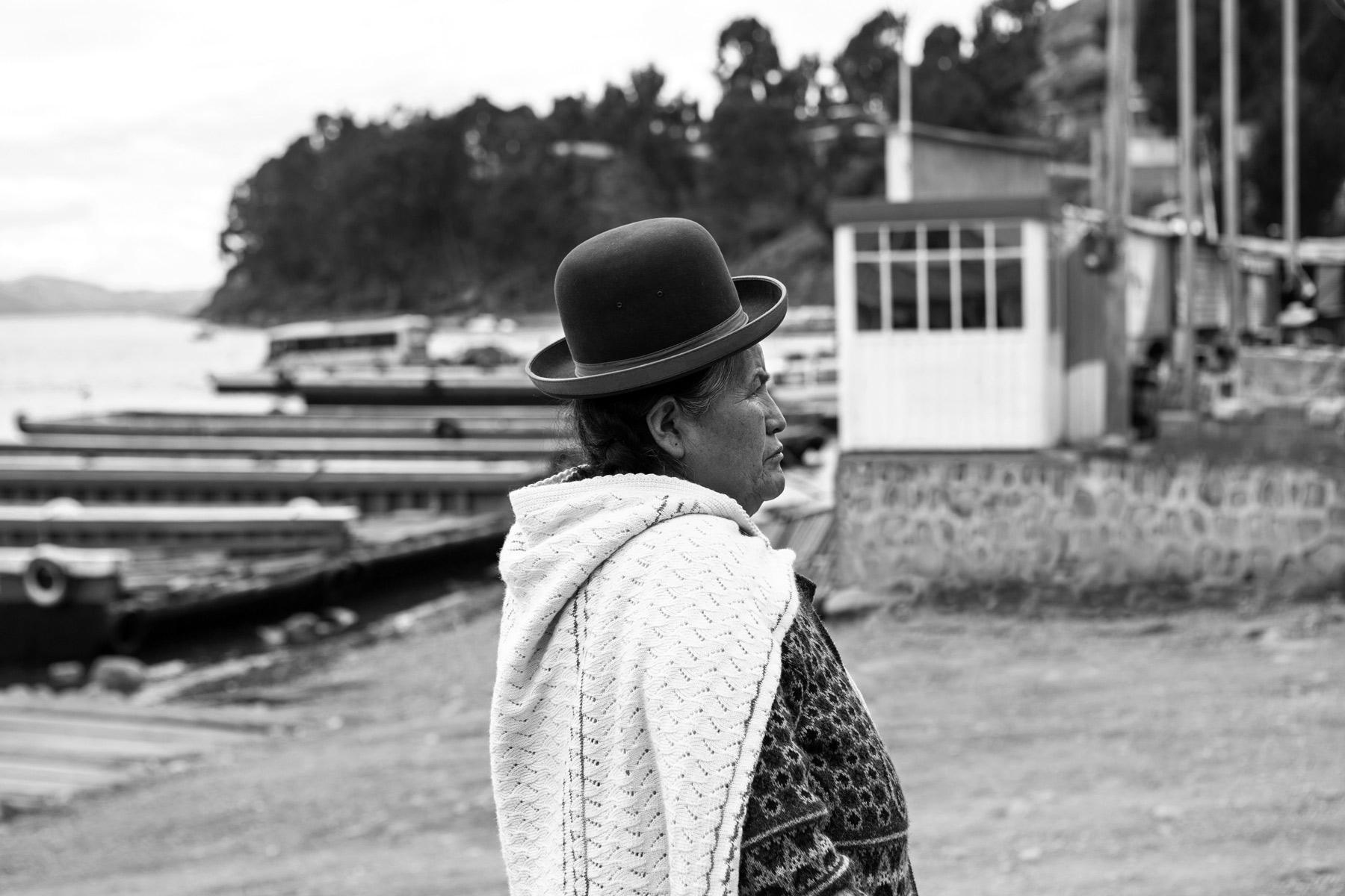 A woman wearing a bowler hat at Lake Titicaca, Peru