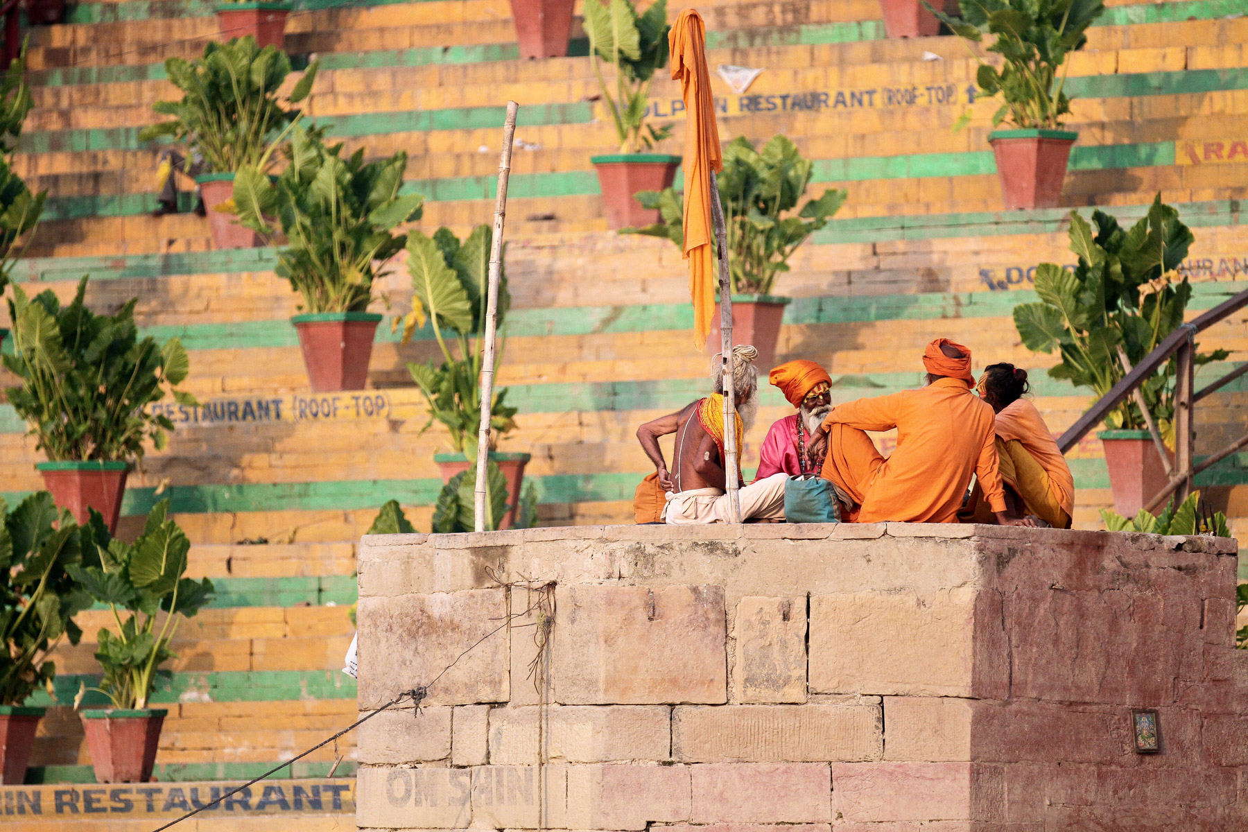 Holy men sitting on the edge of the Ganges River in Varanasi, India