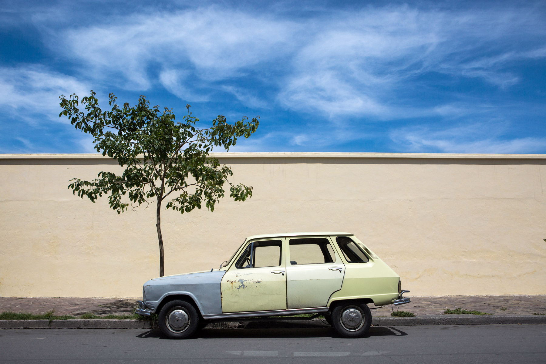 A yellow car in front of a yellow wall in Salta, Argentina