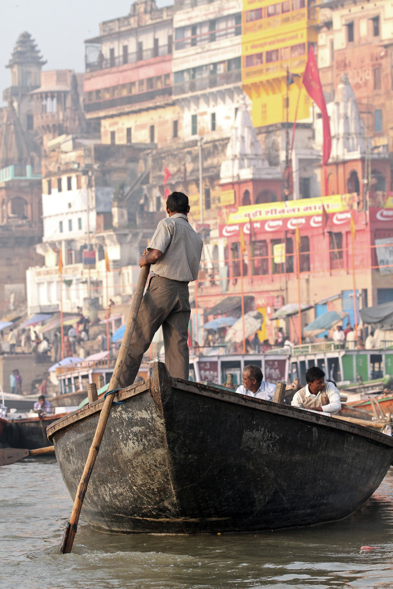 A man steering a boat on the Ganges River in Varanasi, India