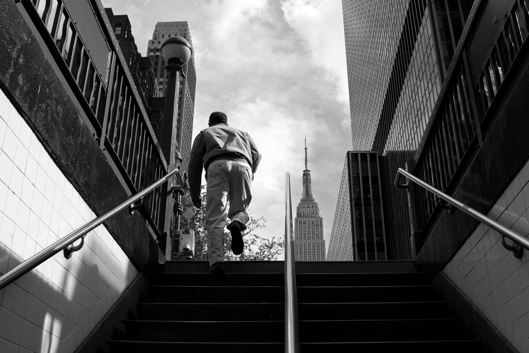 A man walking up stairs from the subway with the Empire State building in the background