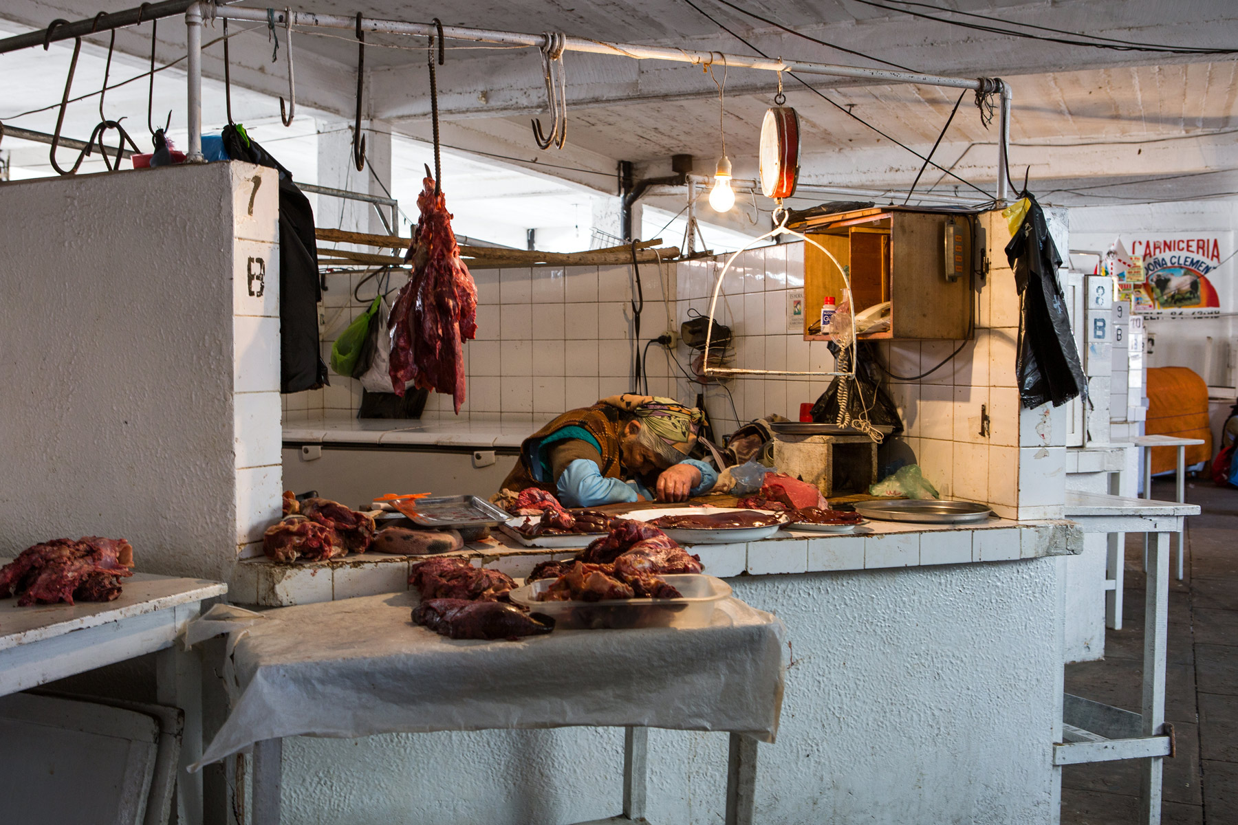 A woman asleep in a market stall selling meat in Bolivia