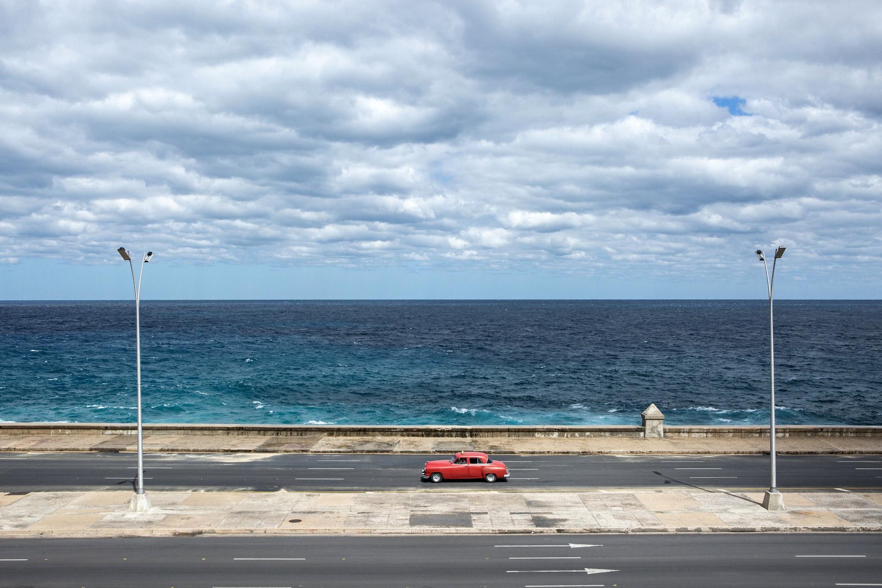 A classic American car driving along the Malecon in Havana, Cuba