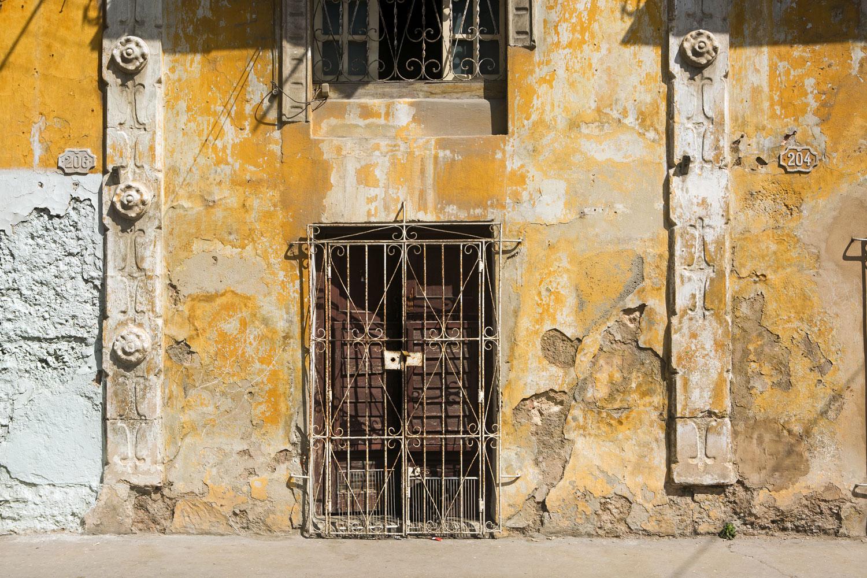 A door of a yellow building in Havana, Cuba
