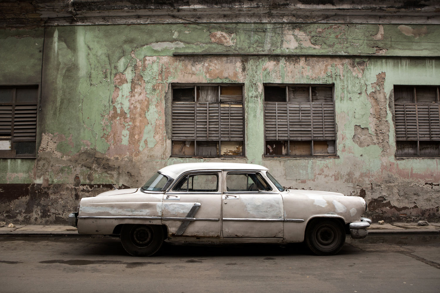 A classic American car in front of a green wall in Centro Havana, Cuba