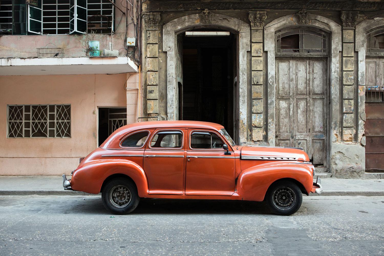 An orange classic American car parked in Centro Havana, Cuba
