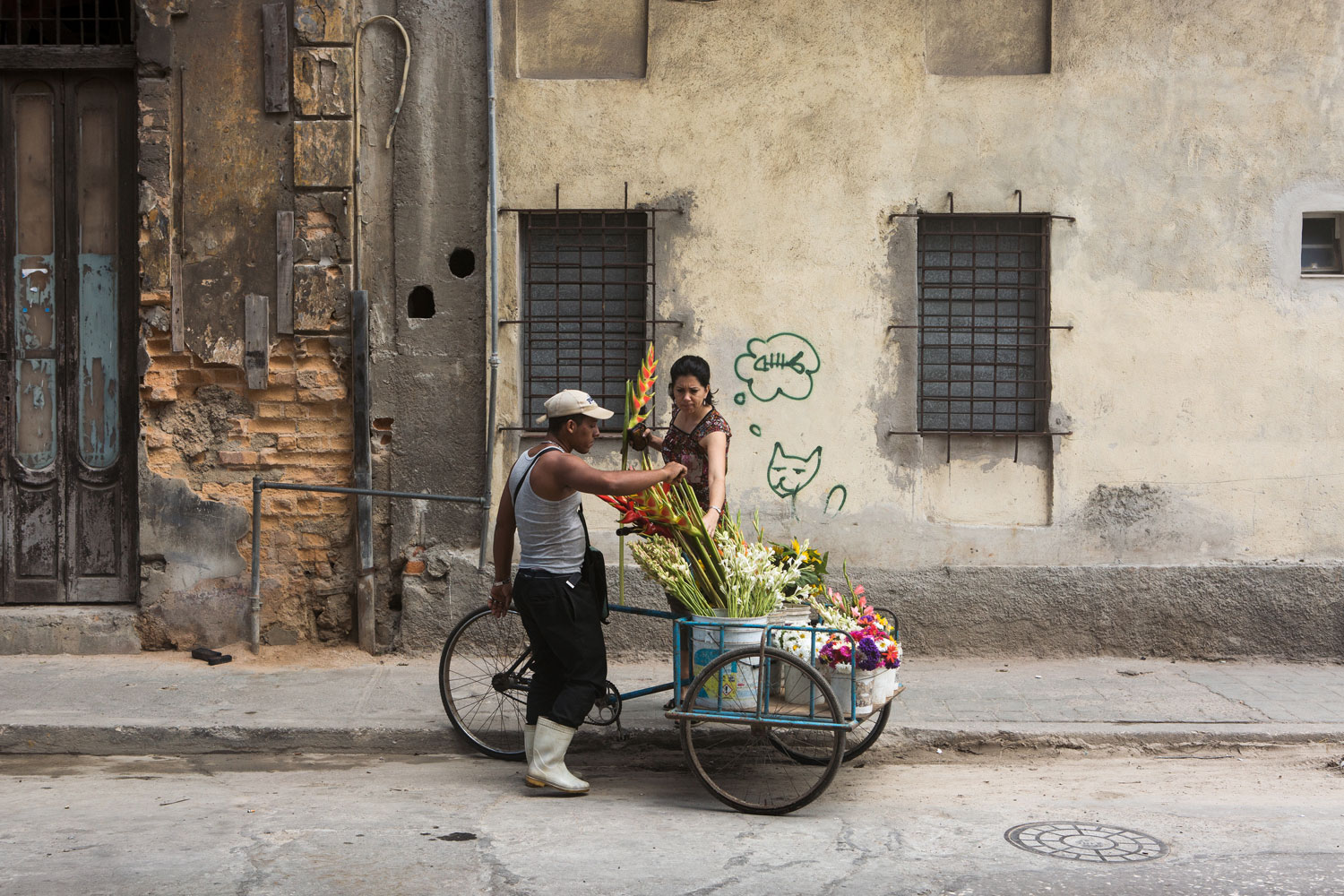 A flower vendor selling flowers to a woman in Centro Havana, Cuba