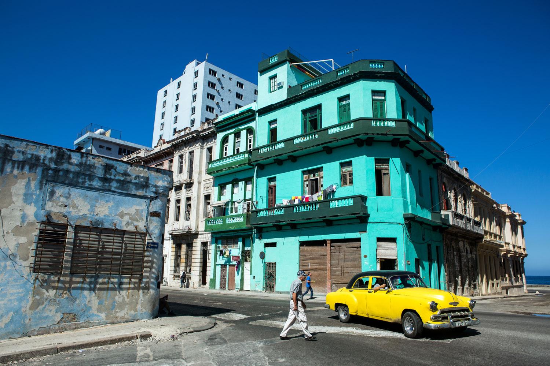 A yellow classic car driving in Centro Havana, Cuba