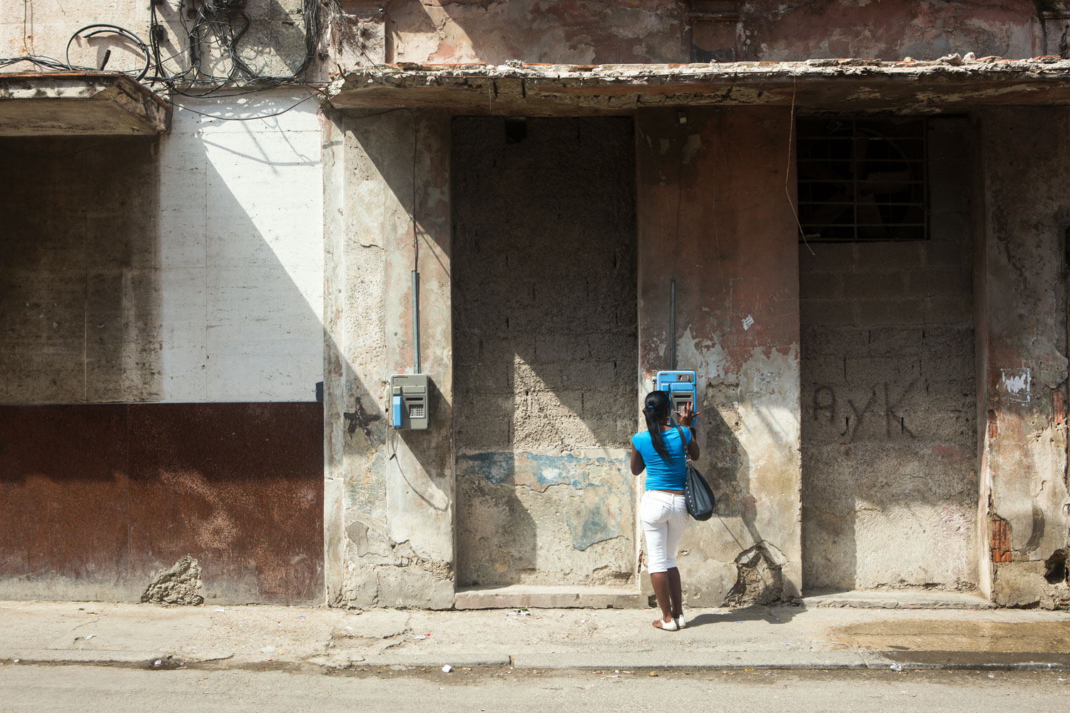 A woman using a payphone in Centro Havana, Cuba