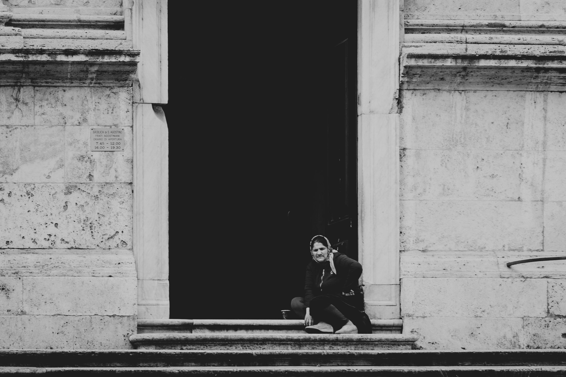 ABOVE:A woman begging on the steps of a church.