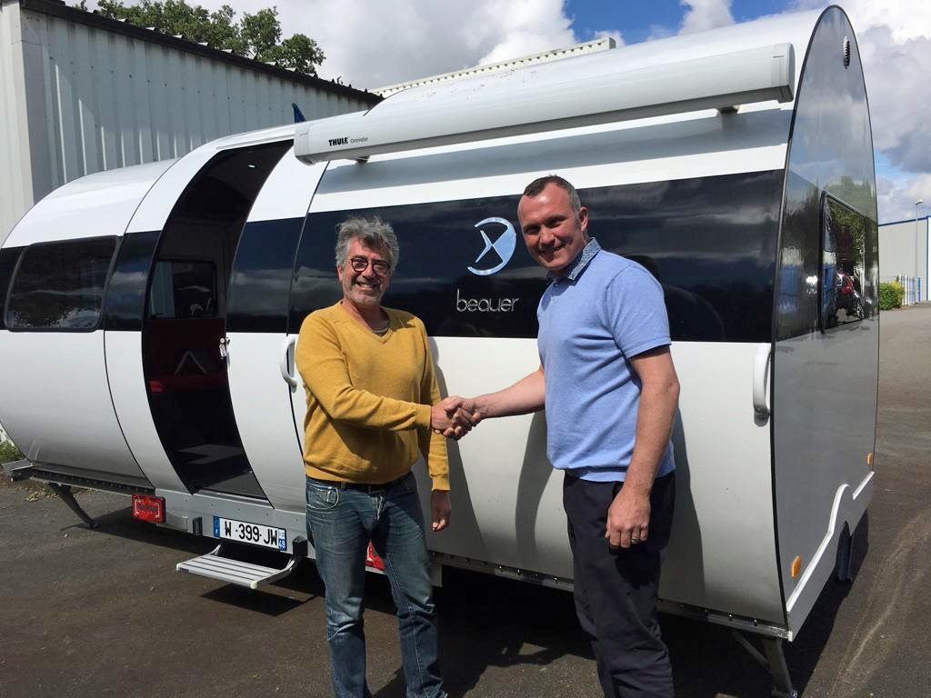Eric beau, CEO Beauer sas (left) and steve young, director rp motorhomes ltd (right) seal the deal in front of a beauer 3x caravan