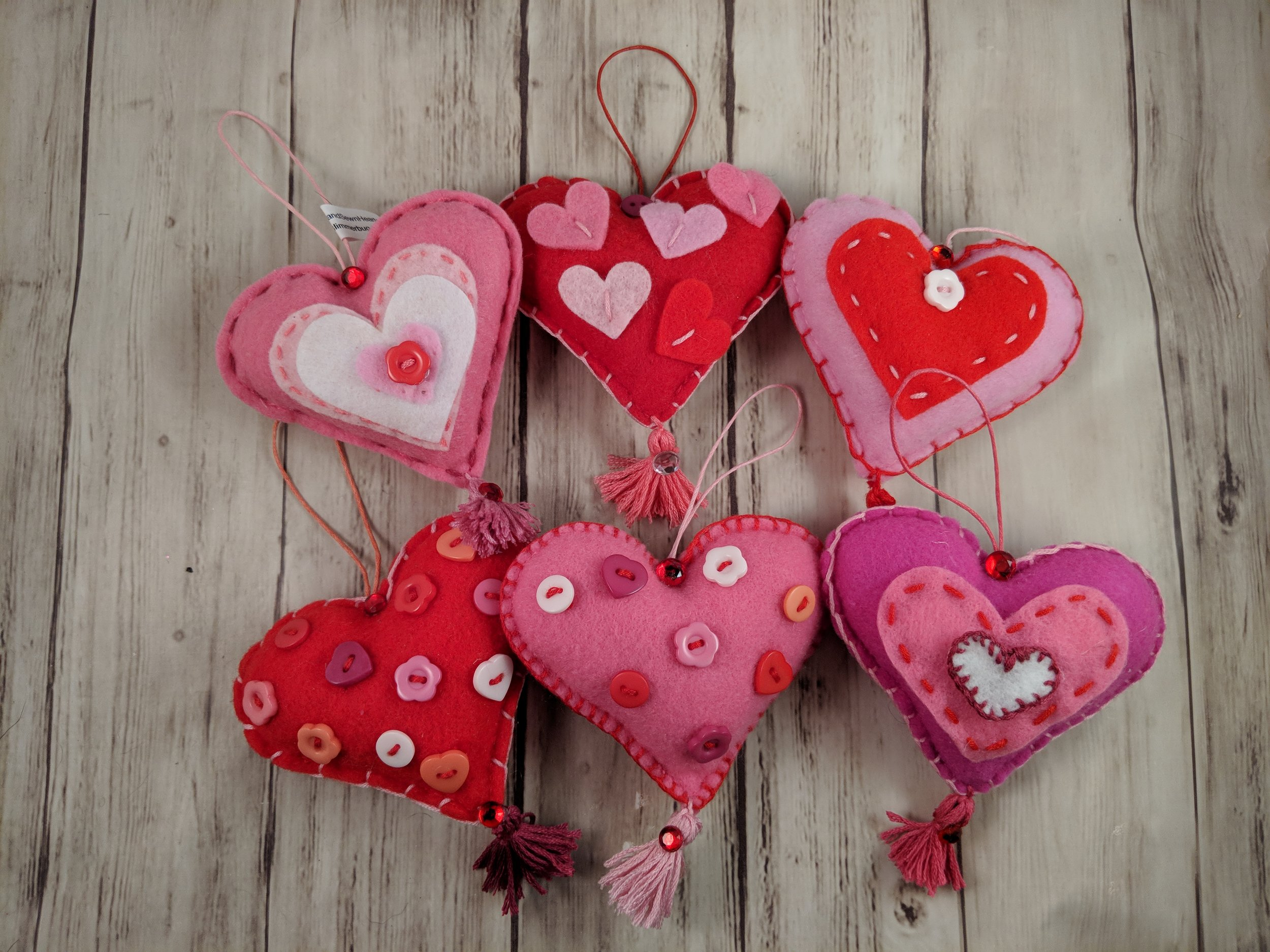 Hand sewn felt heart ornaments decorated with buttons and stitching.