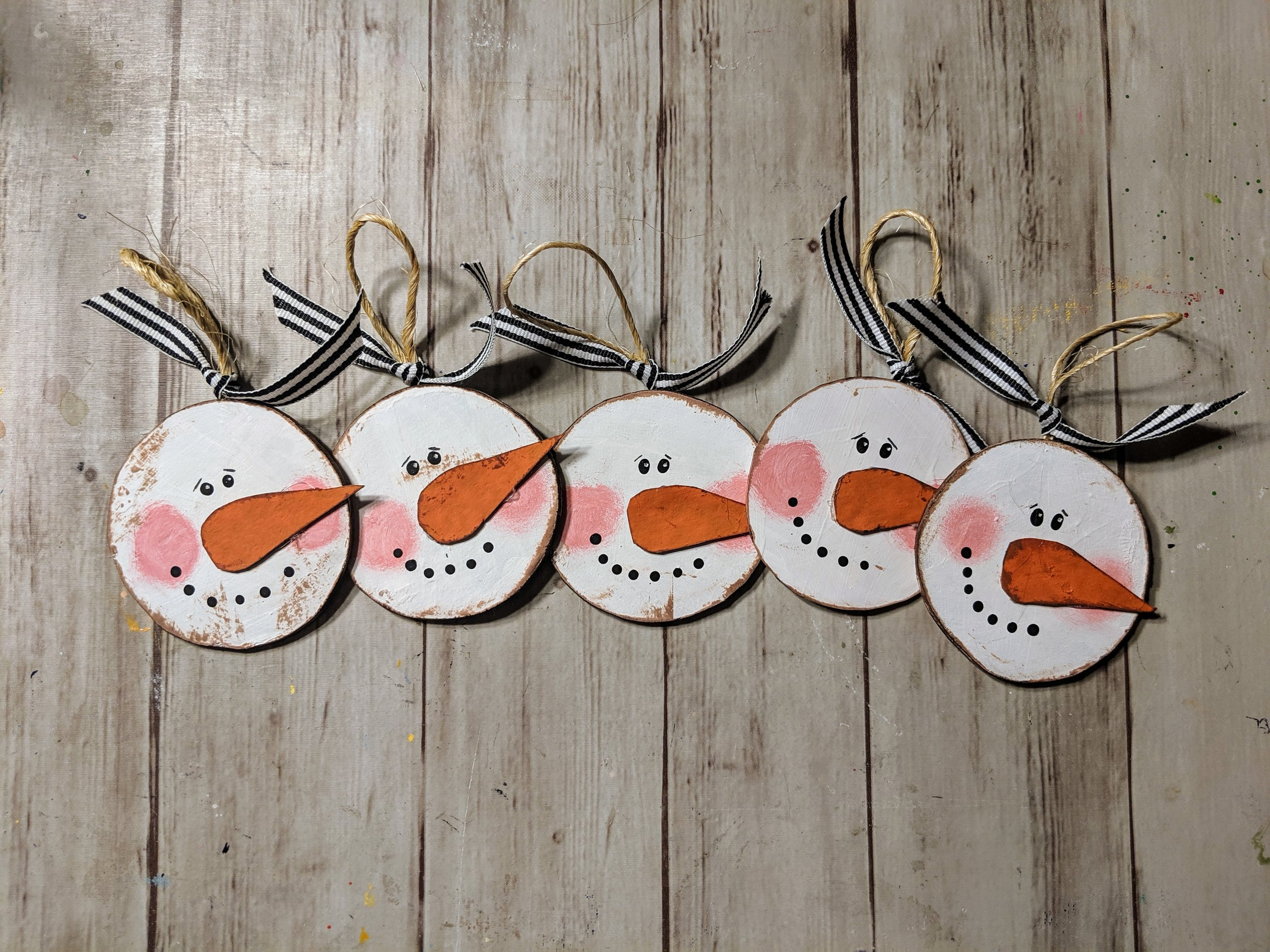 Adorable little snowman ornaments are all handmade from recycled paperboard and decorated with an eye catching black and white ribbon.