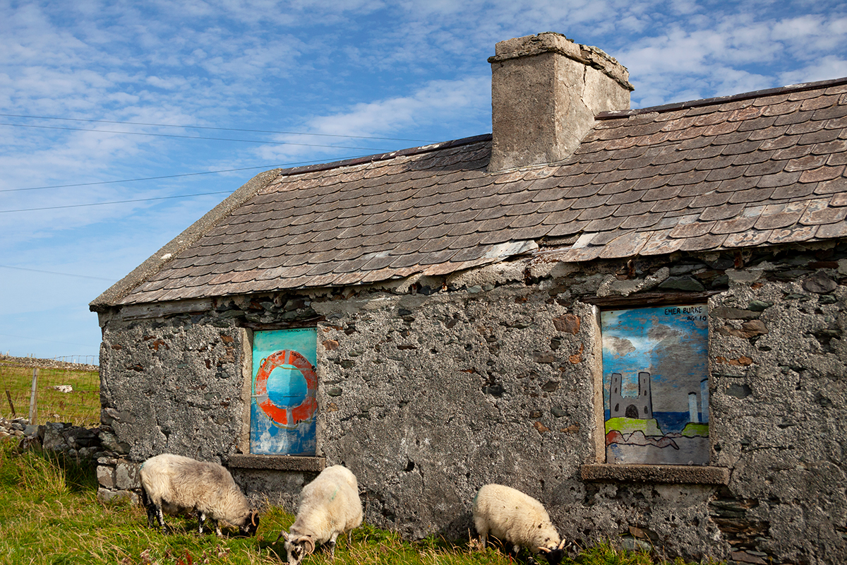 Empty cottage with childrens' artwork in the windows, on Inishbofin island.