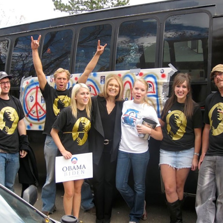 Group of women in front of tour bus with Gloria Steinem