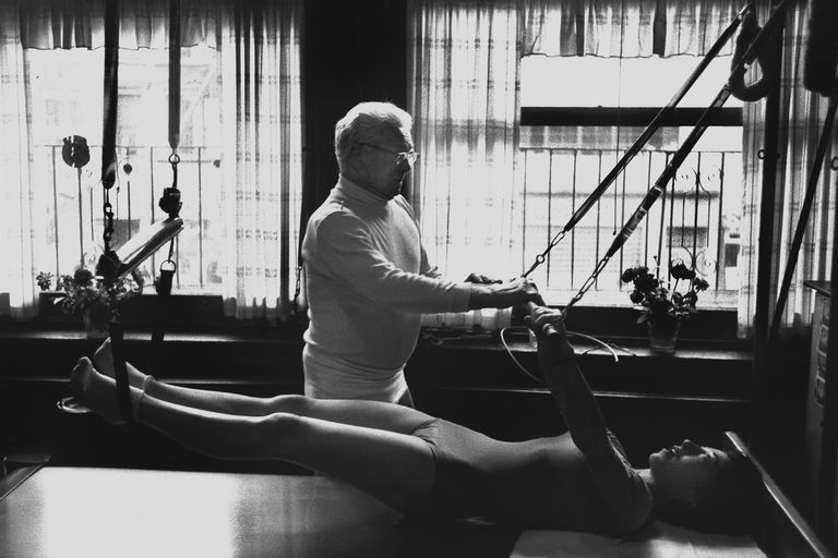 Joseph Pilates  NEW YORK - OCTOBER 1961: Joe Pilates, Inventor, physical fitness guru and founder of the Pilates exercise method instructs a client on the Cadillac and works her through an exercise routine in his 8th Avenue studio on October 4, 1961 in New York City, New York. (Photo by I.C. Rapoport/Getty Images)