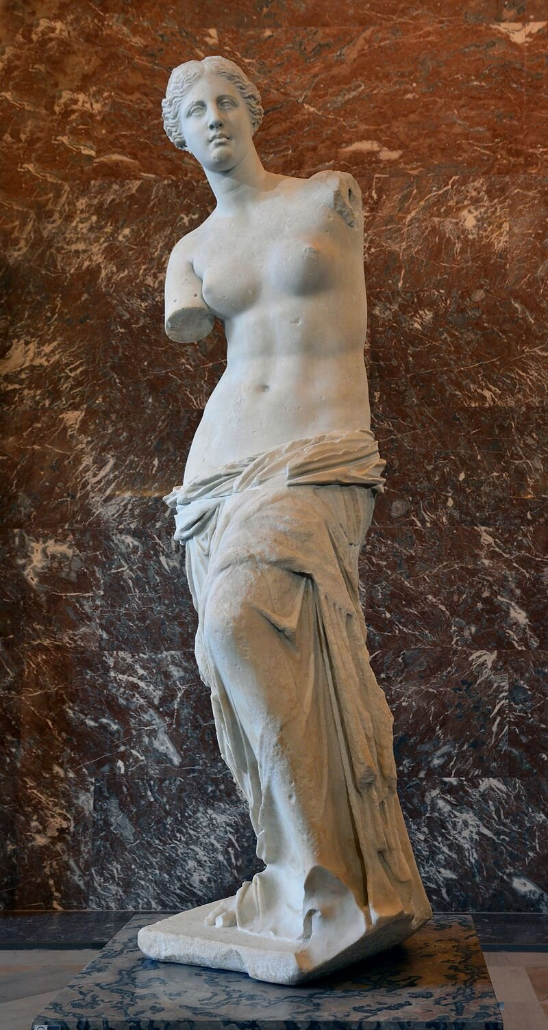 Venus de Milo at the Louvre - This is one of the most iconic images in all of history: the armless Greek masterpiece from the 1st century BCE, Venus de Milo. Her true identity is unknown: she could be the goddess Aphrodite or Amphitrite, but she has inspired modern viewers ever since her discovery on the Greek Isle of Melos in 1820. Look at her spiraling body, enigmatic expression, the drapery just slipping off her hips — this was all created with a block of marble and chisel over 2,000 years ago. What do you make of the Venus de Milo? You cannot know until you stand before her and see her with your own eyes.