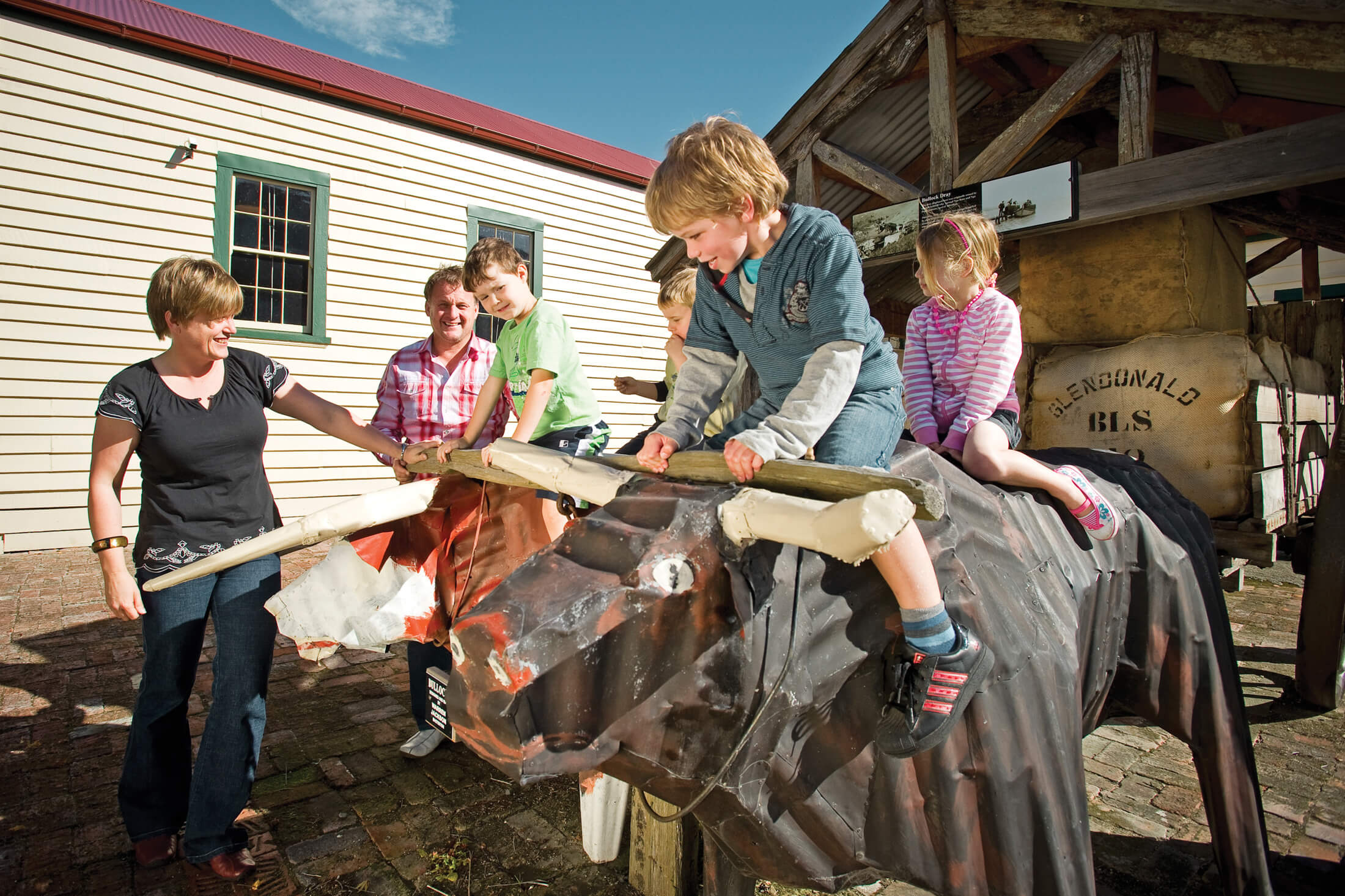 Kids having fun on corrugated iron bullocks outside The Wool Shed. The bullocks are pulling a wagon loaded with wool bales from the Glendonald farm. They were created by Masterton artist Warren Jackson. Behind them is the old Glendonald wool shed that was trucked into Masterton to form part of the museum.