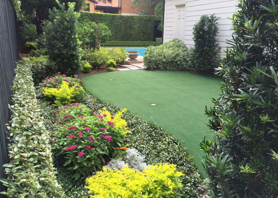 Four cement bowls hold seasonal color and serve as sharp anchor point for the two axes while the undulating lines of the recreational putting green bring an informal element to the garden.