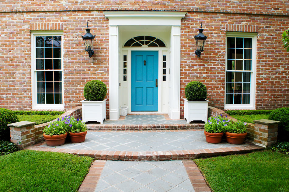 Boxwood globes sit on either side of the front door.
