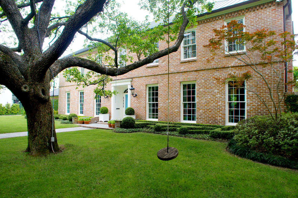 View from an angle shows tree swing and highlights the use of multiple boxwood globes throughout the front garden.