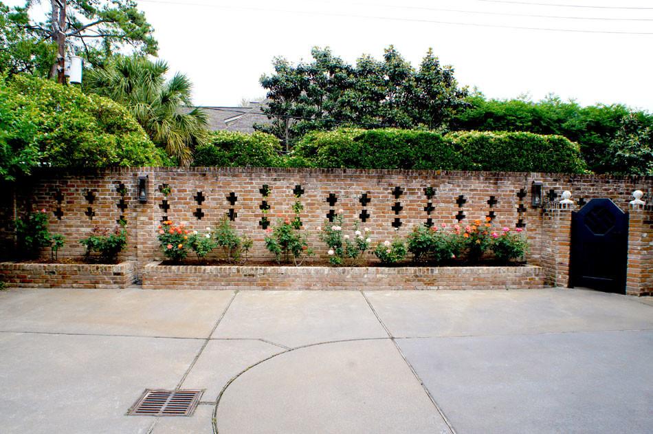Antique rose garden lines the brick wall behind the garage.