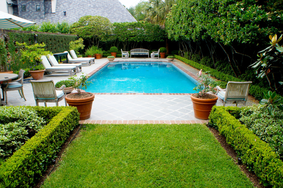 Pool is decorated with container herbs and potted citrus while shapely boxwood hedges frame the space. Blue and white striped cushions are found throughout patio furniture and poolside lounges, giving the setting an english country feel.