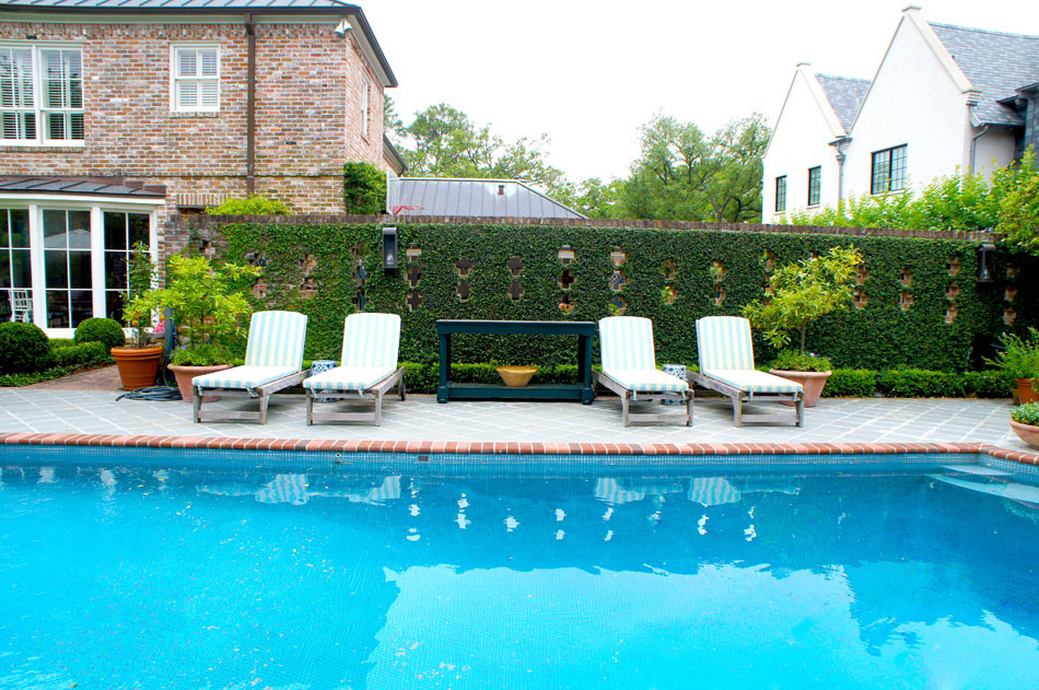 Pool is decorated with container herbs and potted citrus while shapely boxwood hedges frame the space. Blue and white striped cushions are found throughout patio furniture and poolside lounges, giving the setting an english country feel. Fig ivy covers the brick wall.