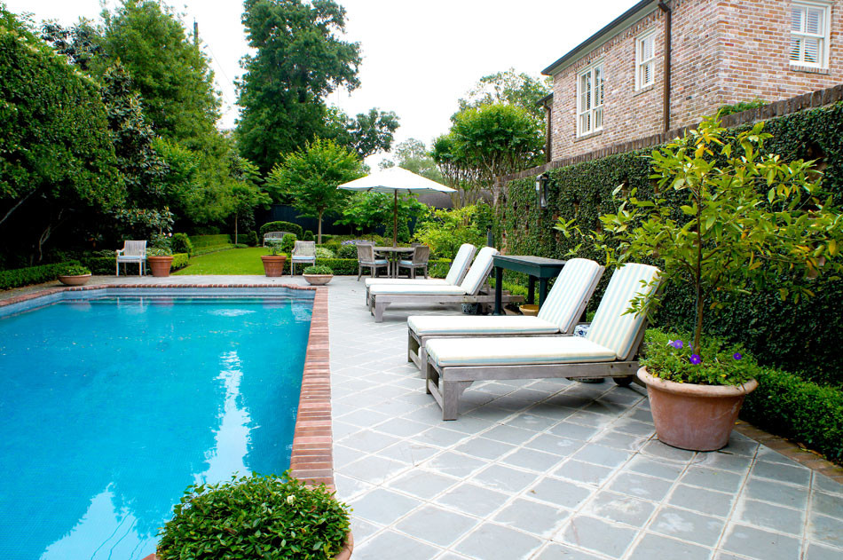 Terra cotta bowls of asian jasmine anchor the corners of the pool. Blue and white striped cushions are found throughout patio furniture and poolside lounges, giving the setting an english country feel.