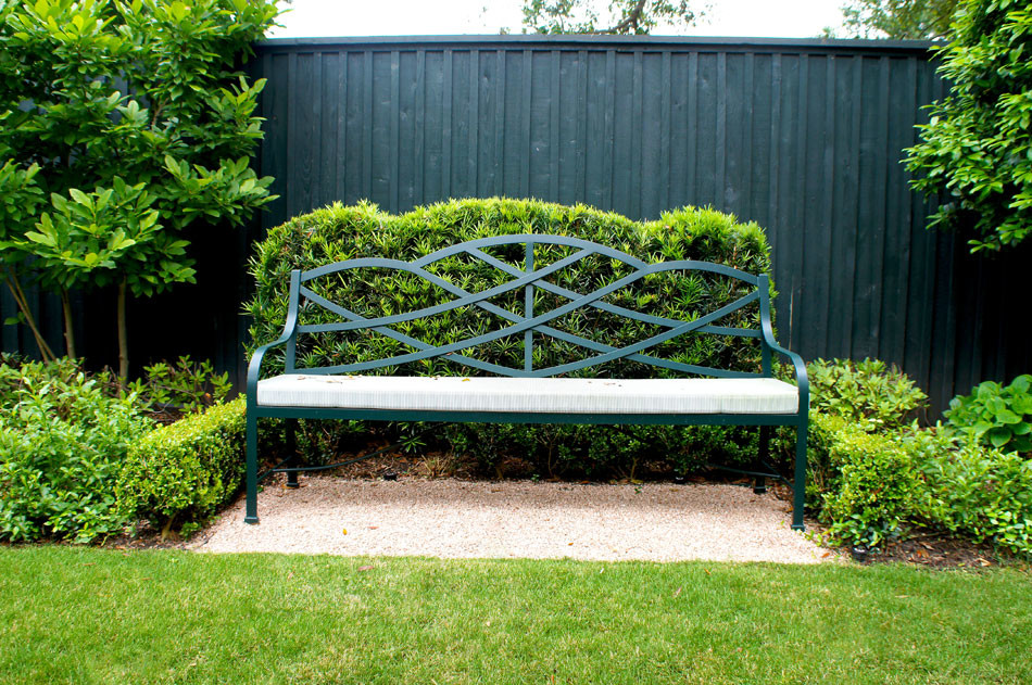 Iron bench sits atop a bed of solado rosa gravel and is framed by a Japanese yew hedge trimmed to mirror the shape of the bench.